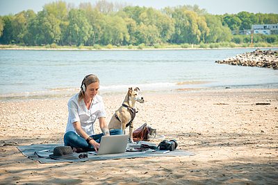 Woman sitting on blanket at a river with dog wearing headphones and using laptop - p300m2005443 von noonland