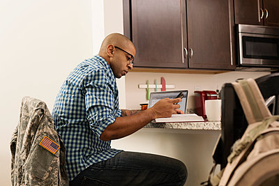 Mixed race soldier using laptop and cell phone on counter - p555m1412432 by Roberto Westbrook