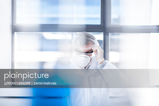 Scientist working in lab putting on protective clothing - p300m1499288 by zerocreatives