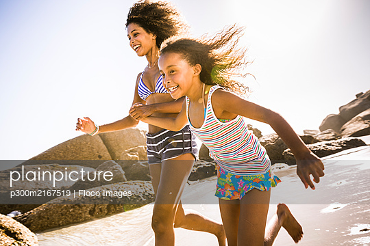 Happy mother and daughter running on the beach - p300m2167519 by Floco Images