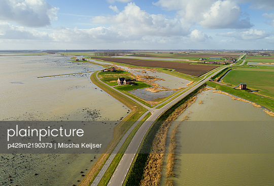 Aerial view of Wadden Sea nature reserve and a road along a dyke in Friesland, The Netherlands.  - p429m2190373 by Mischa Keijser