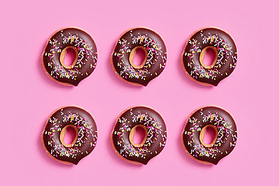 Overhead view of chocolate donuts with sprinkles arranged on pink background - p1166m2025512 by Cavan Images