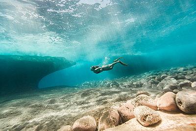 Side view of woman swimming undersea - p1166m2067152 by Cavan Images