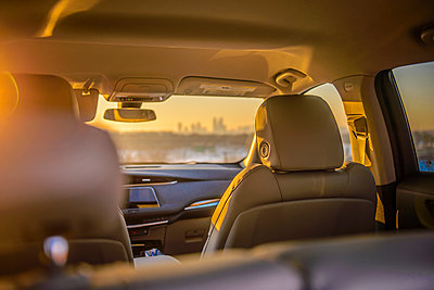 View of city skyline from inside luxury car at sunset - p1166m2096546 by Cavan Images