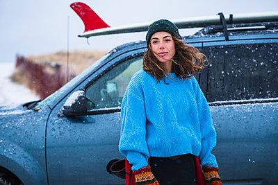 Woman surfer portrait with frozen surfboard - p1166m2177061 by Cavan Images