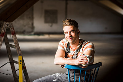Young man sitting on construction site of his new home - p300m1356106 by Uwe Umstätter