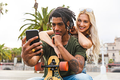 Portrait of multicultural young couple taking selfie with smartphone - p300m2023623 by William Perugini