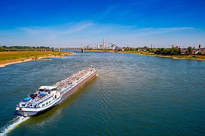Germany, rth Rhine-Westphalia, Dusseldorf, Tanker crossing Rhine with bridge in background - p300m2198207 by Frank Röder