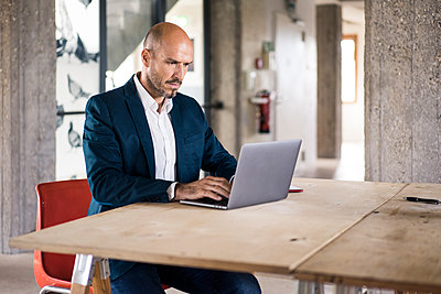 Businessman wearing suit using laptop while working at office - p300m2226974 by Robijn Page