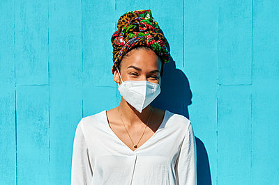Woman wearing protective face mask and headscarf staring while standing against blue wall - p300m2266621 by Kiko Jimenez
