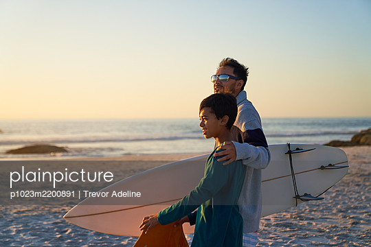 Father and son with surfboard on sunny beach - p1023m2200891 by Trevor Adeline