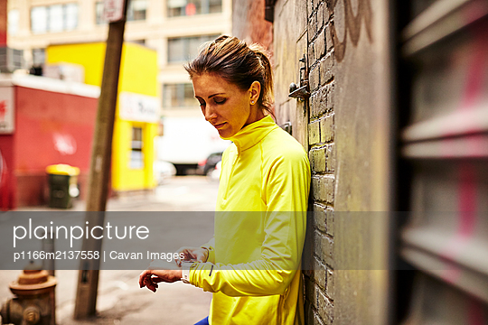 A woman setting her fitness watch on a city street. - p1166m2137558 by Cavan Images