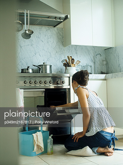 Woman kneeing on cushion while cleaning oven - p349m2167817 by Polly Wreford