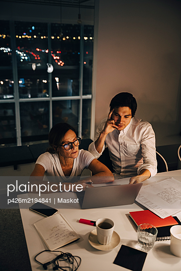 High angle view of female and male entrepreneurs sitting at desk during late night meeting in office - p426m2194841 by Maskot