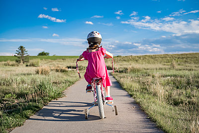 Rear view of girl sitting on bicycle with training wheels against sky during sunny day - p1166m1509631 by Cavan Images