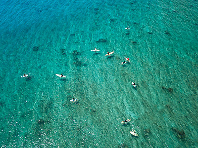 Aerial view of people surfing on sea during sunny day - p1166m2009416 by Cavan Images