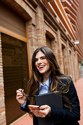 Happy young businesswoman with tablet and cell phone in the city - p300m2070794 by Valentina Barreto