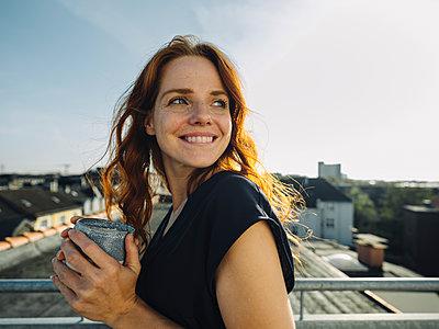Smiling redheaded woman having a coffee break on rooftop terrace - p300m2167260 von Kniel Synnatzschke