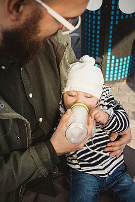 Father feeding baby - p312m2162028 by Amanda Falkman