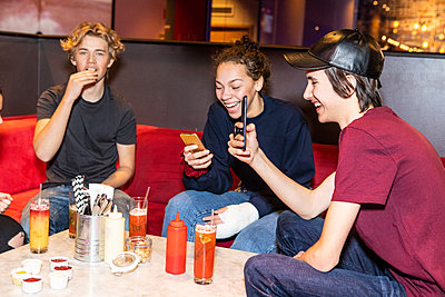 Cheerful teenage friends enjoying while using smart phones at restaurant - p426m1588380 by Maskot