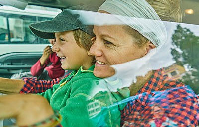 Mother and sons inside vehicle, smiling, view through window - p429m1557373 by Stephen Lux