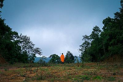Man wearing an orange raincoat contemplates surroundings between Cao Bang and Lang Son, Vietnam, Southeast Asia - p934m1558820 by Sebastien Loffler