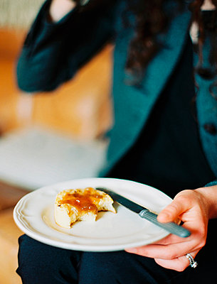 A person holding a plate, holding a half eaten scone with jam. - p1100m876167f by Britt Chudleigh