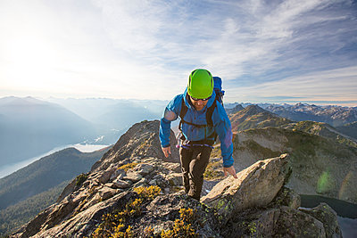 Backpacker scrambles across rocky ridge, British Columbia, Canada. - p1166m2095214 by Cavan Images