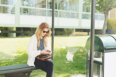 Young woman using phone while waiting at bus stop - p1185m1080571f by Astrakan