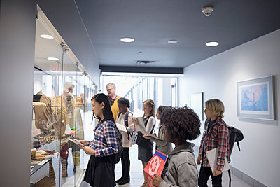 Multi-ethnic students and docent at exhibit on field trip in war museum - p1192m1447265 by Hero Images
