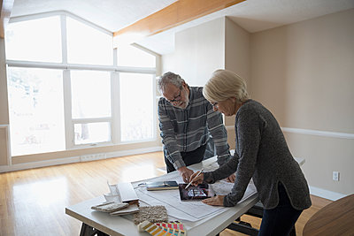 Senior couple planning remodel using digital tablet augmented reality in living room - p1192m1559995 by Hero Images