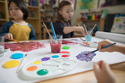 Preschool boy and girl painting in art classroom - p1192m1560116 by Hero Images