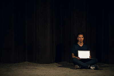 Mid adult man sitting cross-legged on ground, showing blank laptop screen - p300m2029367 von Gustafsson