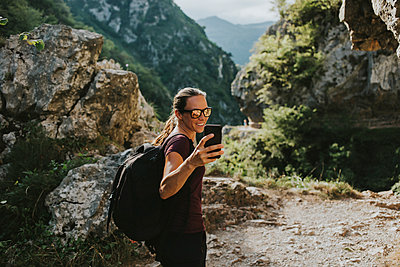 Smiling female trekker taking selfie through smart phone while hiking - p300m2225197 by David Molina Grande