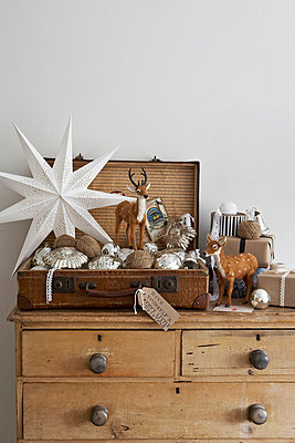 Vintage suitcase with silver Christmas baubles reindeer and gift-wrapped presents on wooden chest of drawers London UK - p349m695314 by Jon Day