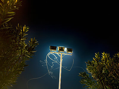 Insect light trails in front of floodlight at night - p429m1494659 by Seb Oliver