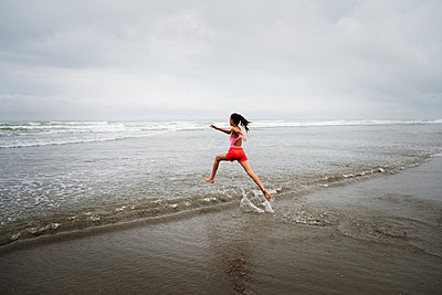 Mixed race girl running into ocean on beach - p555m1312088 by Donald Iain Smith