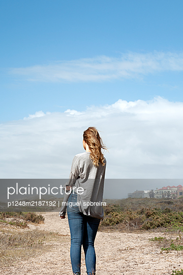 South africa, Woman in Jeans and Cardigan on sandy path - p1248m2187192 by miguel sobreira