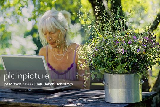 Ältere Frau arbeitet im Garten am Computer - p1418m1571286 von Jan Håkan Dahlström