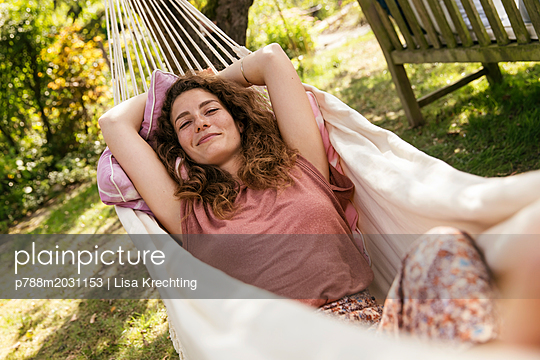 Young woman relaxing in hammock - p788m2031153 by Lisa Krechting
