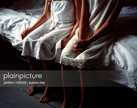Zwei Mädchen sitzen auf der Bettkante - p945m1155029 von aurelia frey