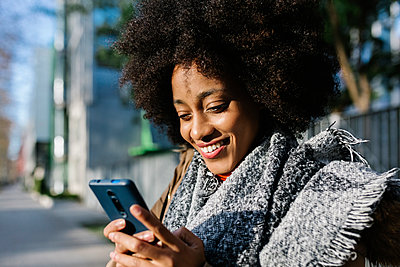Smiling young woman using smart phone on street during sunny day - p300m2257495 by Xavier Lorenzo