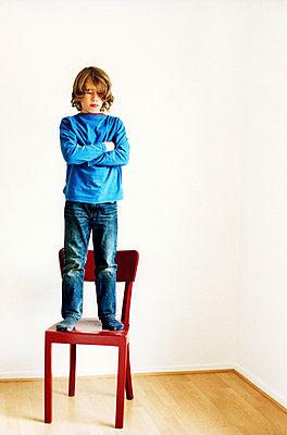 Boy standing on a chair - p879m753500 by nico