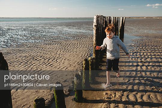 Boy running through water at beach against decaying breakwater pilings - p1166m2130804 by Cavan Images