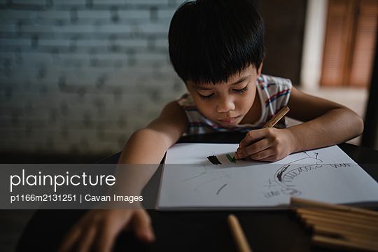 Asian boy drawing with colour pencils - p1166m2131251 by Cavan Images
