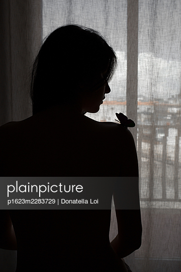 Silhouette of a woman with a butterfly on her arms - p1623m2283729 by Donatella Loi