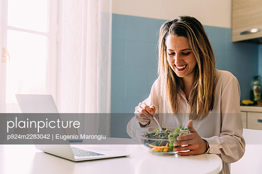 Italy, Woman eating salad in kitchen - p924m2283042 by Eugenio Marongiu