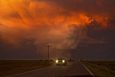Car moving on road against cloudy sky during sunset - p1166m1096420f by Cavan Images