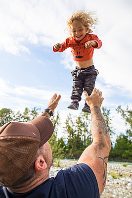Father playfully throwing son up in air - p1166m2202017 by Christopher Kimmel / Alpine Edge Photography