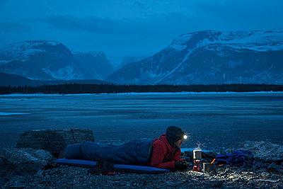 Male hiker preparing food while lying in sleeping bag on mountain at dusk - p1166m2212671 by Cavan Images